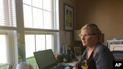 Realtor Michelle Bushée poses at her desk while working from her home in Pittsburgh, Pennsylvania, April 3, 2020. Her weeks used to be very busy but now the entire month of April is empty.