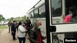 Венесуэльские беженцы пересекают мексикано-американскую границу на автобусе Службы пограничного контроля США. 27 мая 2021 года. Техас.