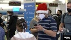 Un pasajero revisa su teléfono celular antes de viajar a Ecuador desde el aeropuerto internacional de Miami. [Foto: Antoni Belchi, VOA]