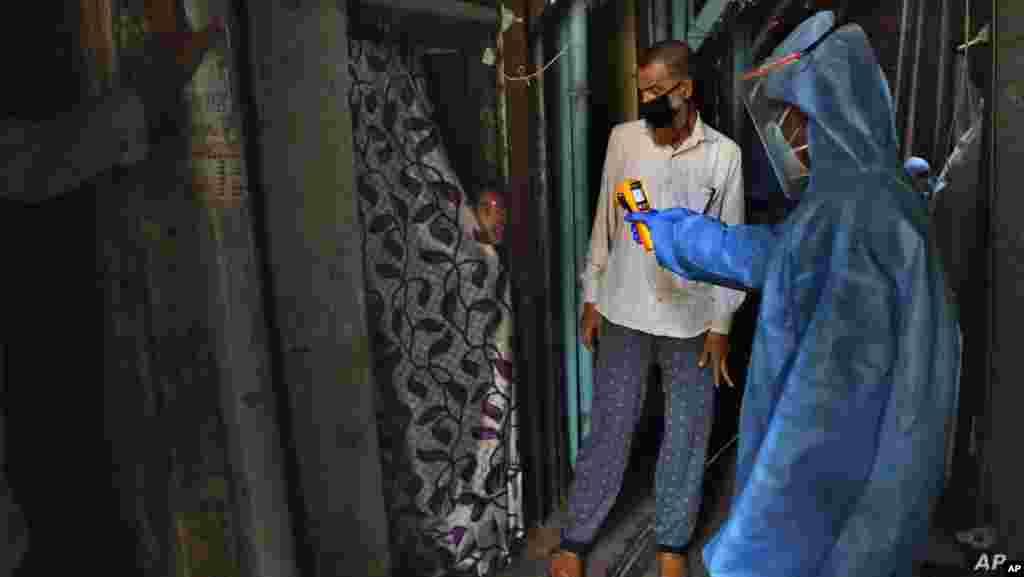 인도 뭄바이의 빈민가에서 보호장비를 착용한 의료진이 소녀의 온도를 측정하고 있다.