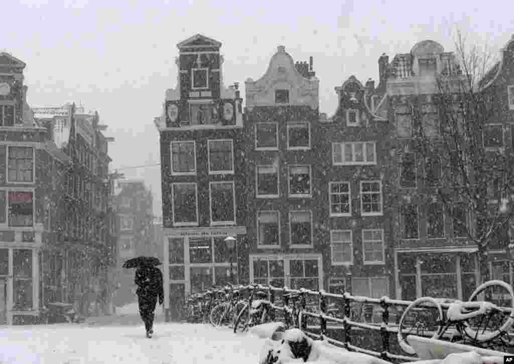 A man crosses a bridge in heavy snow in Amsterdam, Netherlands, February 3, 2012. (AP)