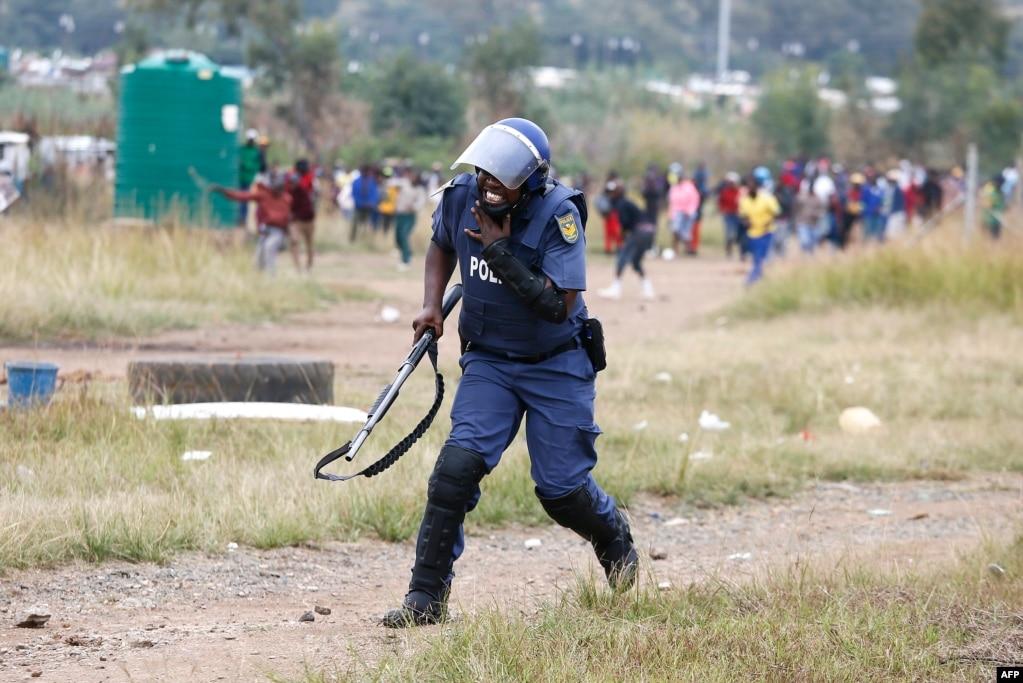 남아프리카 공화국 수도 프레토리아에서 경찰이 물과 전기 공급 부족 항의 시위에 참가한 시민이 던진 공에 맞고 고통스러워 하고 있다.