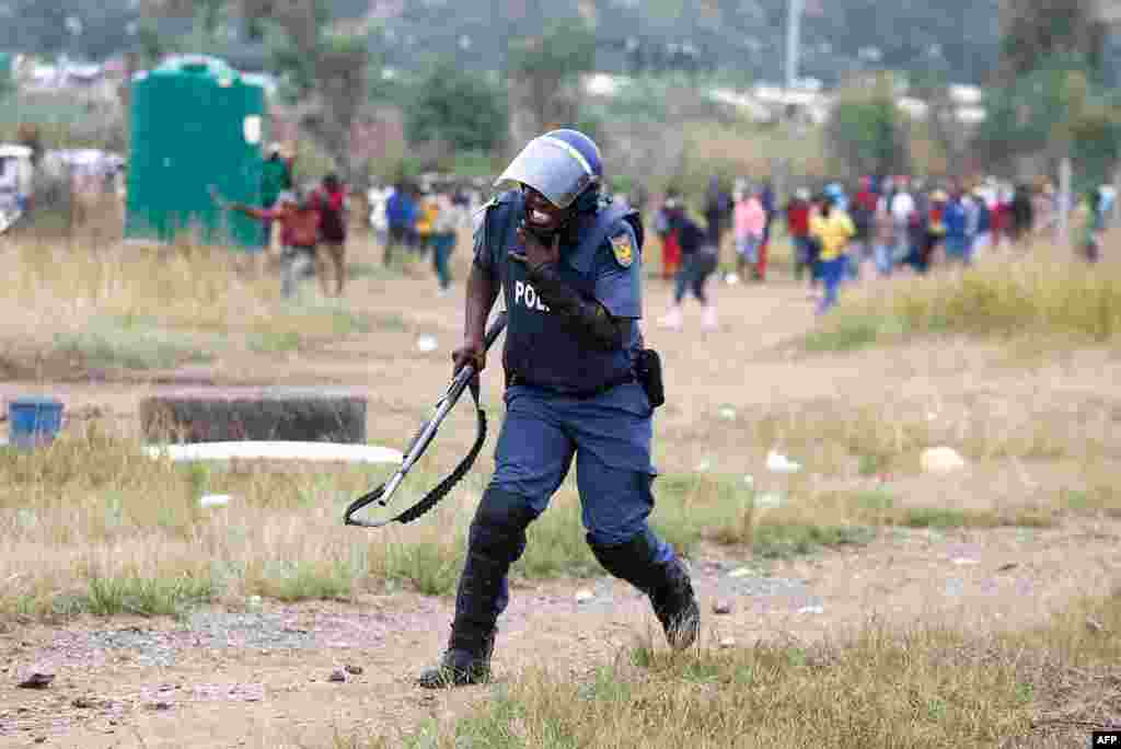 A South African Police Services member reacts after being hit by a rock during a demonstration of Gomora informal settlement community members to protest the lack of service delivery or basic necessities, housing difficulties and lack of public road maintenance in Pretoria.