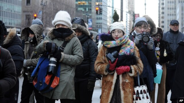 Photographers brave the cold to take pictures of guests arriving during Fashion Week in New York, Feb. 13, 2016.
