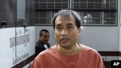 Thai-born American Joe Gordon gestures as he answers a reporter's question upon his arrival at a criminal court in Bangkok, Thailand, December 8, 2011.