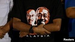 Seorang pendukung mengenakan kaus bergambar politisi Anwar Ibrahim dan Perdana Menteri Mahathir Mohamad saat kampanye di Kuala Lumpur, Malaysia, 16 Mei 2018.