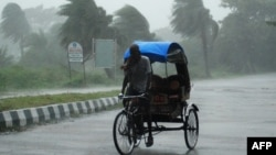 Rickshaw driver plows through heavy rain in Berhampur, about 180 kilometres south of Bhubaneswar, Oct. 12, 2013.