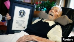 111-year-old Alexander Imich holds a Guinness World Records certificate recognizing him as the world's oldest living man during an interview with Reuters at his home on New York City's upper west side, May 9, 2014. Dr. Imich, who holds a Ph.d in Zoology, was born in Poland on February 4, 1903, fled Poland when the Nazis took over in 1939, survived a slave labor camp in Russia and moved to the United States in 1951 where he became an author on parapsychology.