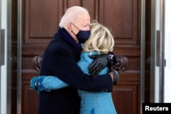 U.S. President Joe Biden and first lady Jill Biden hug as they arrive at the North Portico of the White House in Washington, DC, U.S. January 20, 2021. Alex Brandon/Pool via REUTERS