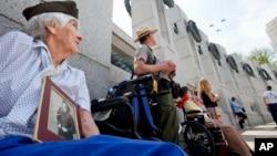 2015年5月8日96岁的二战老兵伊丽莎白·考普拿着自己二战时期的照片观看二战飞机飞过华盛顿纪念碑