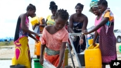 A young girl fetches water at a camp for displaced survivors of cyclone Idai in Beira, Mozambique, April, 2, 2019.