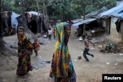 Rohingya Hindu refugees walk through the Kutupalong Hindu refugee camp near Cox's Bazar, Bangladesh, Dec. 17, 2017.