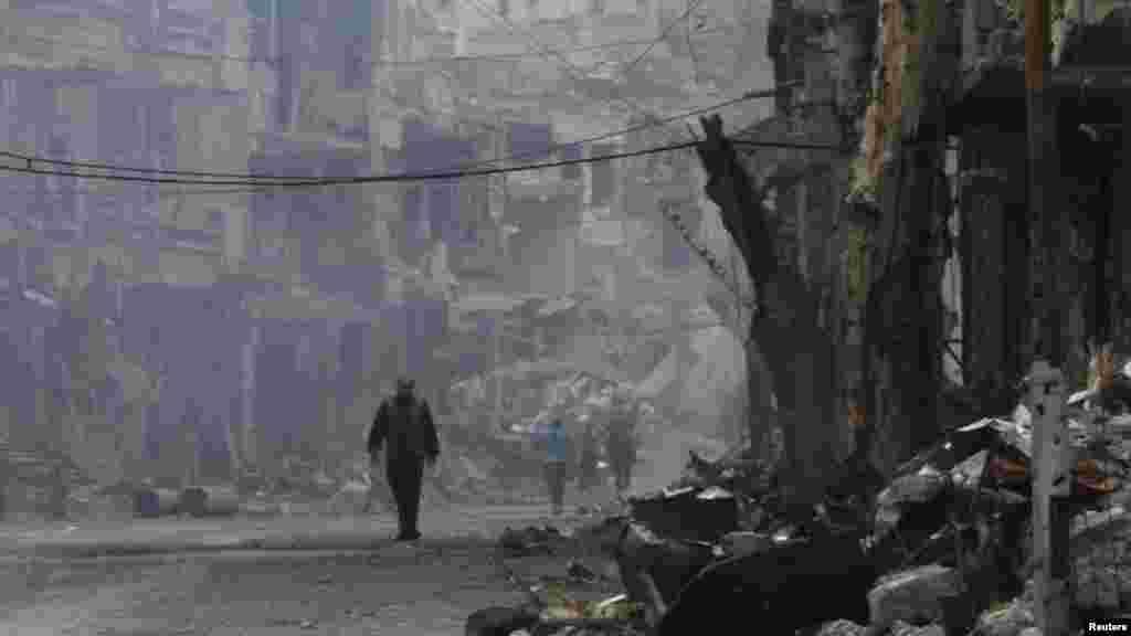 A man walks along a damaged street in Deir al-Zor, Nov. 27, 2013.
