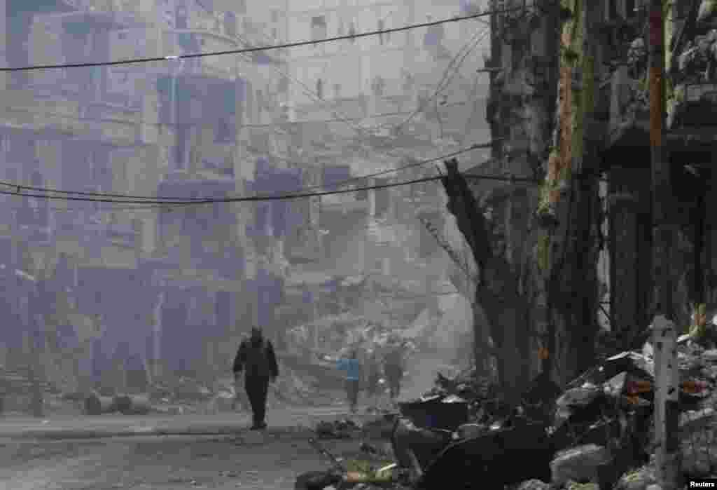 A man walks along a damaged street in Deir al-Zor, Nov. 27, 2013.