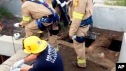 This image from video provided by the Los Angeles Fire Department shows firefighters working where a 13-year-old boy fell through through the small hole at right into a river of sewage in the Griffith Park area of Los Angeles. Jesse Hernandez was swept away Sunday, April 1, 2018, and spent more than 12 hours in the toxic environment of the sewer system before being rescued.