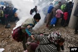 A woman falls as refugees with their children run away after Macedonian police used tear gas to dispearse refugees trying to break the gate to enter Macedonia, Feb. 29, 2016.
