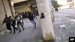 從錄像圖片顯示﹐星期三在敘利亞城市哈馬的示威者逃避軍隊的槍擊。