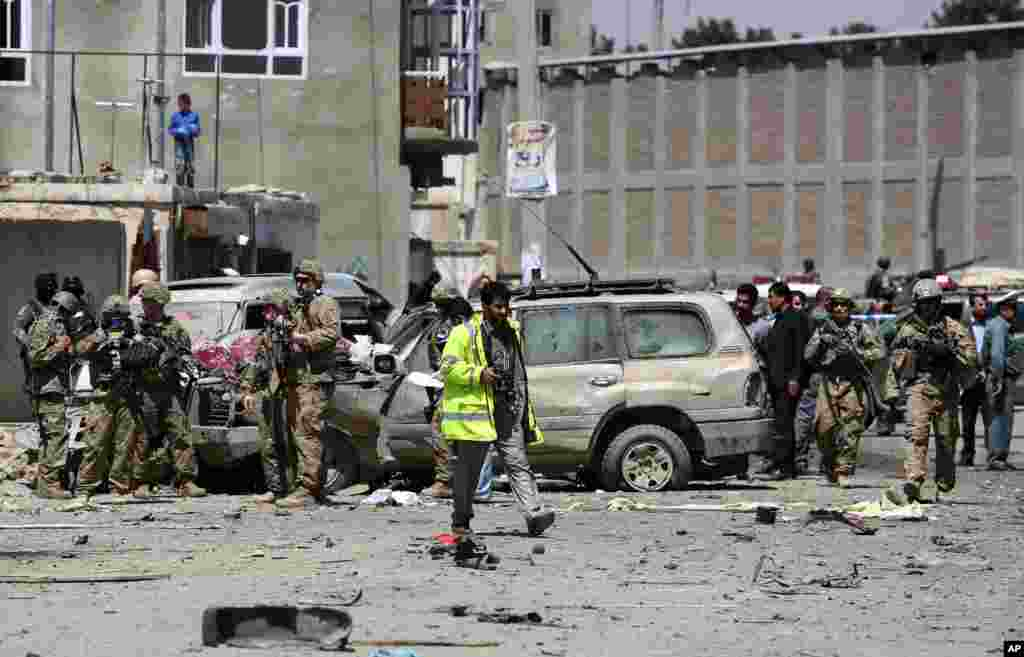 U.S. forces and Afghan security inspect damages at the site of a suicide bombing attack near Kabul's international airport in Kabul, Afghanistan. A suicide bomber detonated an explosives-packed car near the airport, wounding at least 16 civilians.