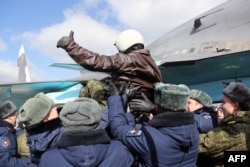 A handout picture taken on March 15, 2016 and released by the Russian Defence Ministry shows a Russia's air force pilot, who returned from the Hmeimim military base in Syria's Latakia province.