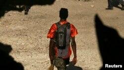 Yon manm gang kap mache ak yon gwo zam nan men l apre yon lese frape ak militè Nasyon Zini yo Foto achiv: 22 desanm 2006. (REUTERS/Eduardo Munoz)