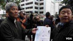 日方代表(左)接受抗议信(美国之音申华拍摄)