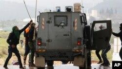 Des manifestants palestiniens attaquent un véhicule militaire israélien lors d'affrontements après les protestations contre l'expansion du quartier juif de Halamish, dans le village de Nabi Saleh, en Cisjordanie, près de Ramallah, le vendredi 3 mars 2017.