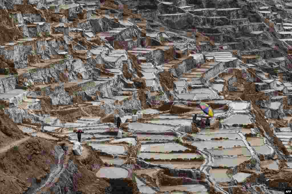 People work at the Maras salt-evaporation ponds, 48 km northeast of Cusco, Peru. Salt pools are one of the tourist attractions in the Cusco area.
