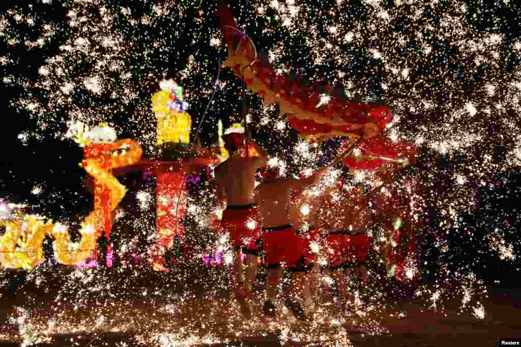 Folk artists perform a fire dragon dance under a shower of sparks from molten iron, ahead of the Chinese Lunar New Year, in Shangqiu, Henan province, China, Feb. 14, 2018.
