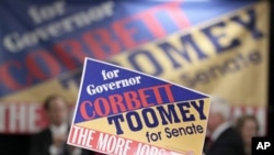 A supporter holds up a campaign sign as Pennsylvania Republican gubernatorial candidate Tom Corbett, Lt. Gov. candidate James Cawley and Pennsylvania Republican Senate candidate Senate Pat Toomey, appear during a rally in Pa., 01 Nov. 2010.