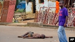 The lifeless body of a man lays unattended in the street as locals suspect him of dying from the deadly Ebola virus, as government warns the public not to leave Ebola victims in the streets in the city of Monrovia, Liberia, Tuesday, Aug. 5, 2014. A seco