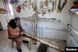 Local craftsman Slanbek, 63, makes traditional horsehide skis on the outskirts of Altay, Xinjiang Uighur Autonomous Region, China, Jan. 25, 2018.