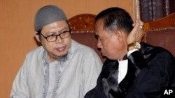 Zainal Anshori (kiri), perwakilan dari JAD, didampingi oleh pengacaranya, mengikuti sidang vonis terhadap JAD di Pengadilan Negeri Jakarta Selatan, Selasa (31/7).