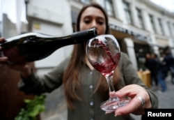 Whether moderate amounts of wine are really good for your heart is debated among health experts. Here, a shop assistant pours wine during a wine festival in Tbilisi, Georgia, 2017. (REUTERS/David Mdzinarishvili).
