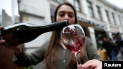 FILE - A shop assistant pours wine during a wine festival in Tbilisi, Georgia, Oct. 15, 2017.