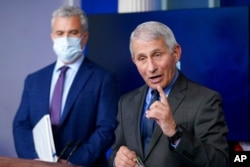 FILE - Dr. Anthony Fauci, director of the National Institute of Allergy and Infectious Diseases, speaks alongside White House COVID-19 Response Coordinator Jeff Zients during a press briefing at the White House, April 13, 2021.