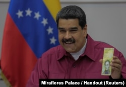Venezuela's President Nicolas Maduro holds a 100,000 bolivar note as he speaks during a meeting with ministers in Caracas, Venezuela, Nov. 1, 2017.