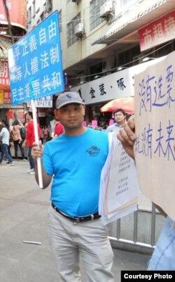杨崇去年三月在广州街头参与公民举牌活动(微博图片)
