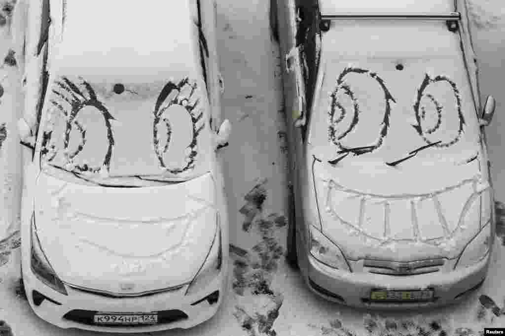 Faces are scrawled on cars covered with snow near a residential building in Krasnoyarsk, Russia.