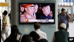 South Korean passengers watch a news reporting about the North Korea's army chief Ri Yong Ho's departure on a TV screen at the Seoul train station in Seoul, South Korea, July 17, 2012.