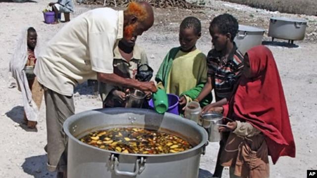 Somali children from southern Somalia, receive cooked food in Mogadishu, Somalia, Monday, Aug 15, 2011