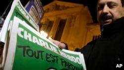 Penjual koran memasang tabloid Charlie Hebdo di kiosnya di Nice, Perancis Selatan (14/1). (AP/Lionel Cironneau)