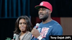 First lady Michelle Obama looks at Cleveland Cavaliers' basketball player LeBron James as he speaks at The University of Akron