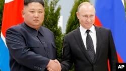 Le président russe Vladimir Poutine, à droite, et le leader de la Corée du Nord, Kim Jong Un, se serrent la main, avant leur entretien à Vladivostok, en Russie, le jeudi 25 avril 2019.