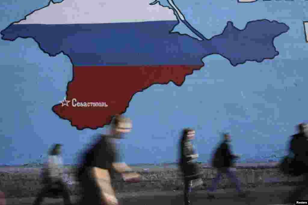 People pass a mural showing a map of Crimea in the Russian national colors on a street in Moscow, March 25, 2014.