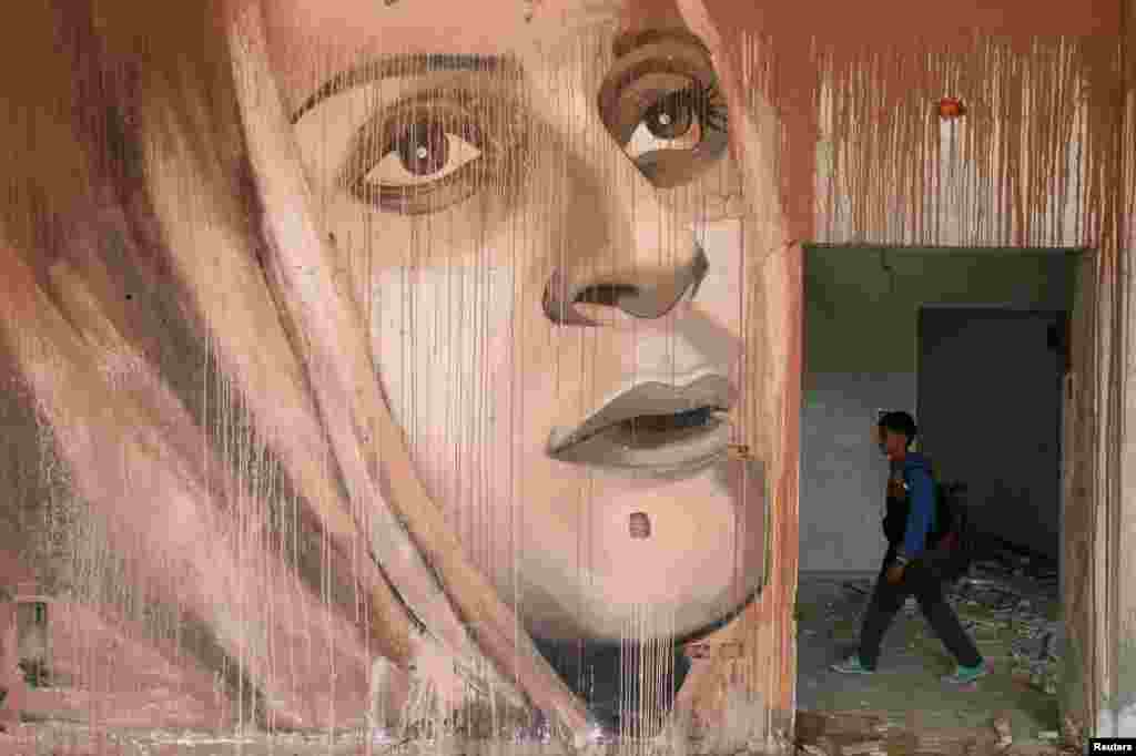 A schoolboy walks near a mural painted by Palestinian artist Ali Al-Jabali in the remains of a building destroyed in former Israeli air strikes, in Gaza City.