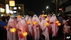 People wear ghost costumes as they join a Halloween Parade in the Philippines, 2013. (AP Photo/Aaron Favila)