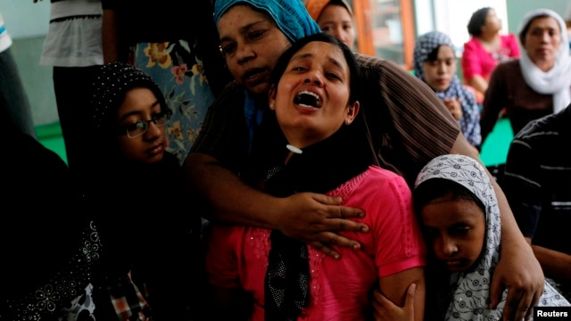 Tin Tin Kyaw (2nd R) cries near the body of her husband Soe Min, a 51-year-old man who was killed in a recent riot, at a mosque in Mandalay July 3, 2014.