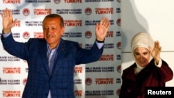 Turkey's Prime Minister Recep Tayyip Erdogan celebrates his election victory flanked by his wife Ermine in front of his party's headquarters in Ankara August 10, 2014.