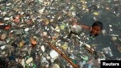 """Seorang anak mengumpulkan botol-botol plastik bekas untuk dijual di Pantai Marunda, Jakarta (foto: dok). Sebuah panel iklim PBB Senin (9/8) mengatakan bahwa perubahan iklim """"benar-benar disebabkan oleh aktivitas manusia""""."""