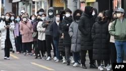 ពលរដ្ឋនៅទីក្រុងថេហ្គូ (Daegu) តម្រង់ជួរទិញម៉ាស់នៅហាងលក់ទំនិញមួយកន្លែងក្នុងតំបន់ពាណិជ្ជកម្ម Dongseongro នៅទីក្រុងថេហ្គូ កូរ៉េខាងត្បូង ថ្ងៃទី២៧ ខែកុម្ភៈ ឆ្នាំ២០២០។
